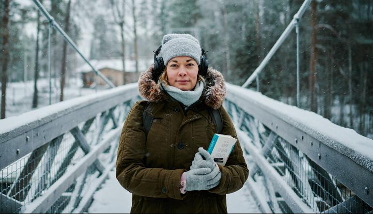 Kirjastojen podcastit. Nainen seisoo talvisessa maisemassa korvillaan kuulokkeet ja sylissä kirjoja. Kuva Ilkka Vuorinen / Kirjastot.fi