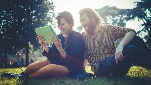 Videoiden ja podcastien tekstitys – 10 käytännön neuvoa. Nuori nainen ja mies nurmikolla katsomassa tablettia