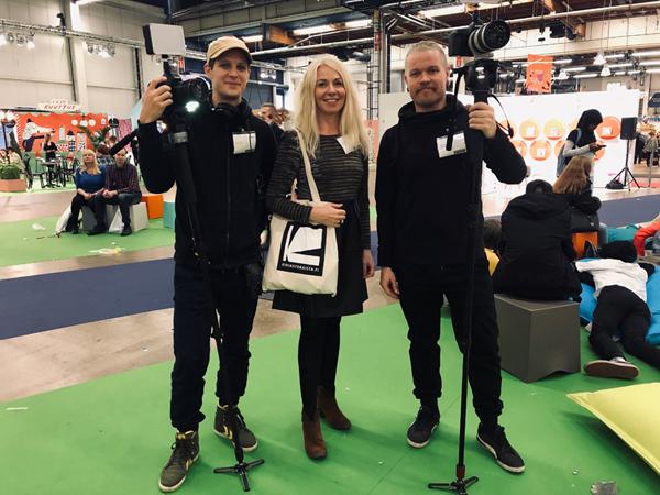 Panu Somerma, Riitta Taarasti ja Mikko Helander eli Kirjastokaistan työntekijät seisomassa vihreällä matolla. Kuvaajilla on kamarat kädessä.