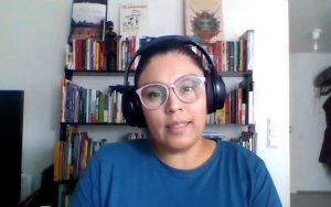 Nainen puhuu kuulokkeet päässään.
