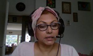 Nainen puhuu kuulokkeet korvillaan.
