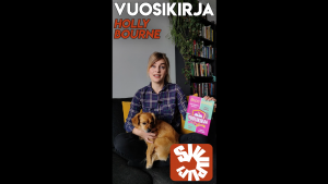 Nainen näyttää kirjan kantta koira sylissään.
